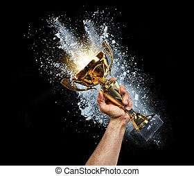 Man holding up a gold trophy cup with powder explosion on...