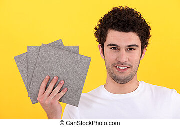 Man holding up tiles