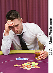 Man holding whiskey glass at poker table