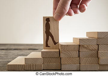 Man holding with his fingers wooden domino with shape of businessman
