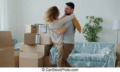 Man is holding woman in arms turning laughing having fun expressing love and care in new apartment with boxes during relocation. People and housing concept.