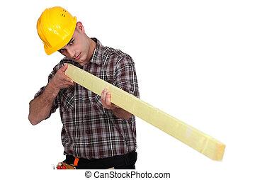 Man holding wooden beam