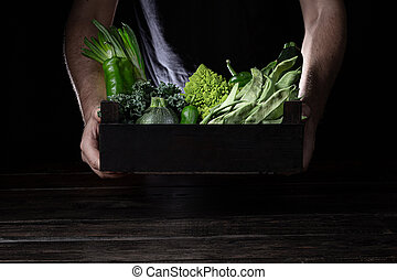 Man holding wooden box with green vegetables on dark background with copy space.