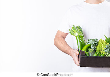Man holding wooden box with green vegetables on white background with copy space.