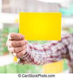 Man holding yellow sign at supermarket