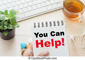 Man holding You Can Help message on book and keyboard with a hot cup of tea, macaroon on the table. Can be attributed to your ad.