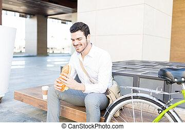 Man Holding Yummy Snack On Bench
