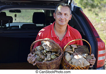 Man holds 2 baskets with mushrooms
