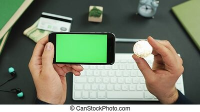 Man holds a black smartphone with green screen over a working table and a golden Bitcoin