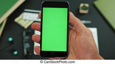 Man holds a black smartphone with green screen over a working table