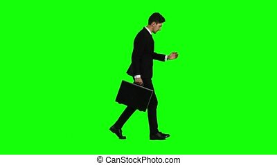 Man holds a briefcase in his hand, he rushes over it. Green screen