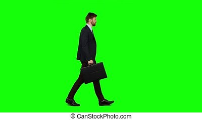 Man holds a briefcase in his hand, he rushes over it. Green...