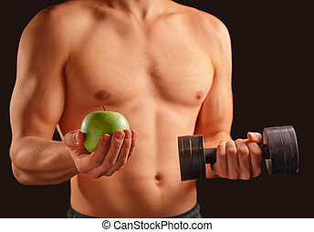 Man holds apple and dumbbell