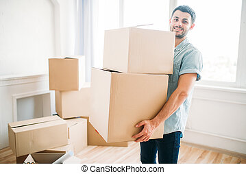 Man holds boxes in hands, moving to new house