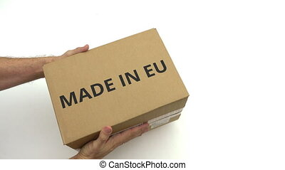 Man holds carton with MADE IN EU text - Man holds carton...