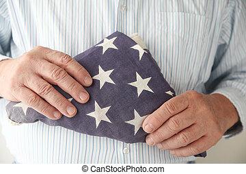 man holds folded American flag