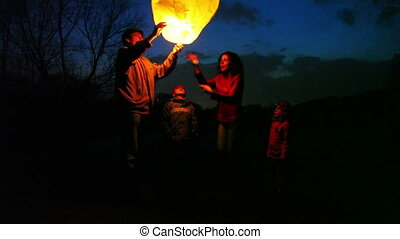 man holds glowing chinese lantern at night, its wife joking forces hands air, son and daughter look, part2