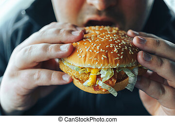 Man holds hamburger in both hands