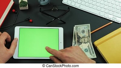 Man holds hundreds of dollars in his arm and then types something on the green screen of a tablet