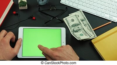 Man holds hundreds of dollars in his hand and then types something on the green screen of a tablet
