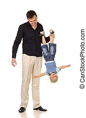 Man holds little boy upside down