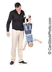 Man holds little boy upside down