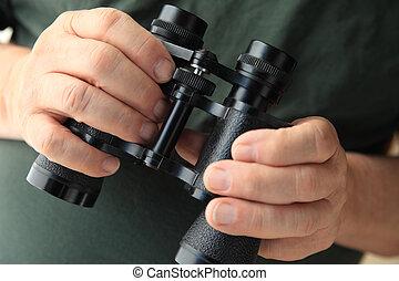 Man holds old pair of binoculars