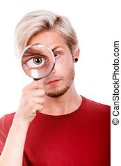 man holds on eye magnifying glass looking through loupe