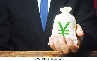 Man holds out a Yen yuan money bag. Provision of money on credit, grant. Project financing. Donations. Financial social assistance. Payment purchases, profits dividends. Business investment