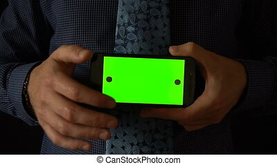 Man holds smartphone to camera with green screen