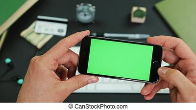Man holds smartphone with green screen over a working table and taps something on it