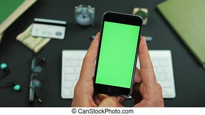 Man holds smartphone with green screen over a working table