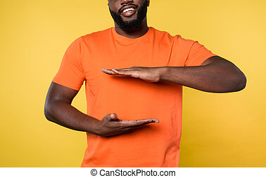 Man holds something with hands. Concept of protection. Yellow background