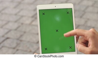 Man holds tablet with green screen