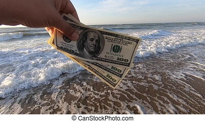 Man holds three hundred dollar in his hands on a background