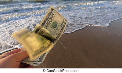 Man holds three hundred dollar in his hands on a background of the sea and white foam with waves and blue sky close-up. move due to strong wind. Slow motion