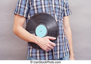 Man holds vinyl record in his hand