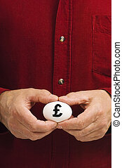 Man holds white egg with the British pound symbol written on