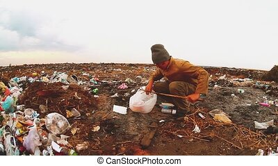 man homeless in a landfill homeless looking for food among...