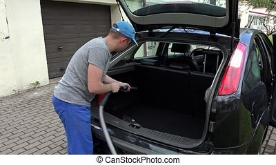 man hoover car boot with vacuum cleaner. - man hoover car...