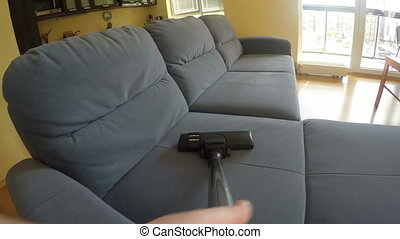 man hoover dust sofa - Man hand hoover dust from blue...