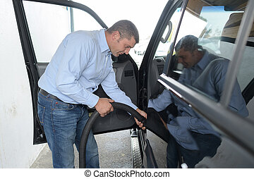 man hoovering or cleaning the car