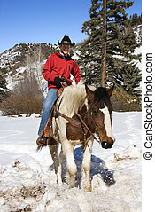 Man horseback riding in snow. - Young Caucasian man...