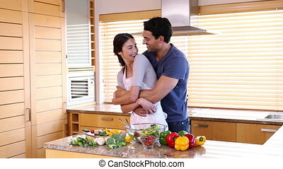 Man hugging his girlfriend in the kitchen