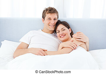 Man hugging his girlfriend on their bed