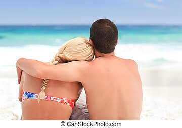 Man hugging his girlfriend while th