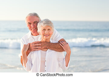 Man hugging his wife on the beach