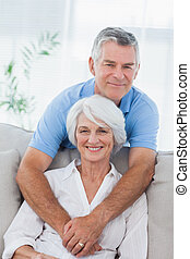 Man hugging his wife who is sitting on the couch