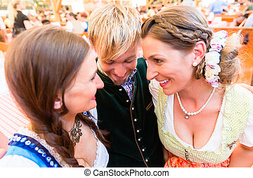 Man hugging two dirndl wearing women in Bavarian beer tent -...