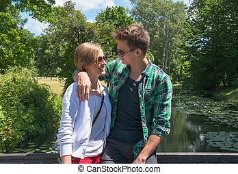 Man hugs a girl on the bridge in a park.